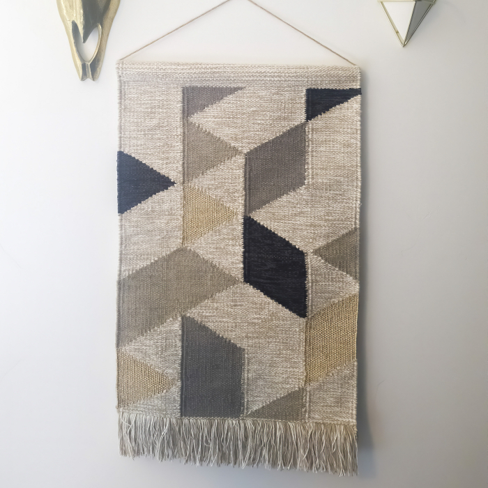 Square frame Woven tapestry metal bull head and plant hanger decorations against white wall. The woven wall hanger has a geometric pattern design and fringes.
