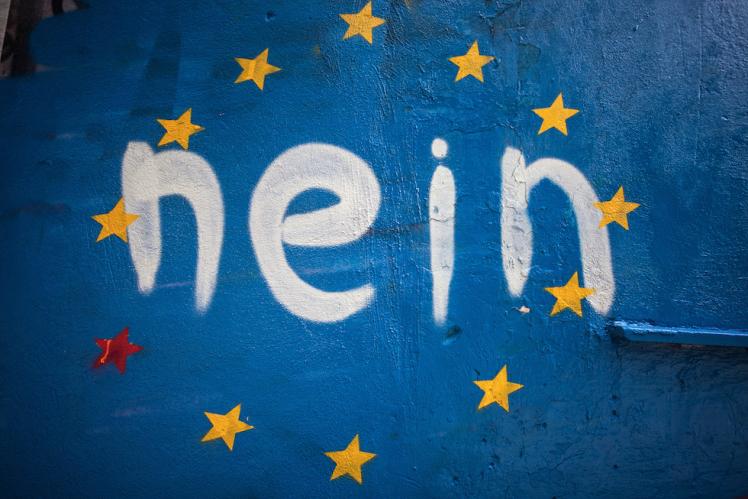 """Un graffito con la bandiera europea e la scritta Nein, che significa """"No"""" in tedesco ma ricorda anche """"Sì"""" (Nai) in greco, Atene, 30 giugno 2015. (Socrates Baltagiannis/picture-alliance/dpa/AP Images)"""