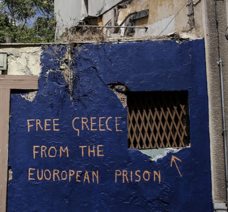 """Il muro di una casa abbandonata con scritto """"Grecia libera dalle prigioni europee"""", Atene, 18 giugno 2015. (AP Photo/Yorgos Karahalis)"""