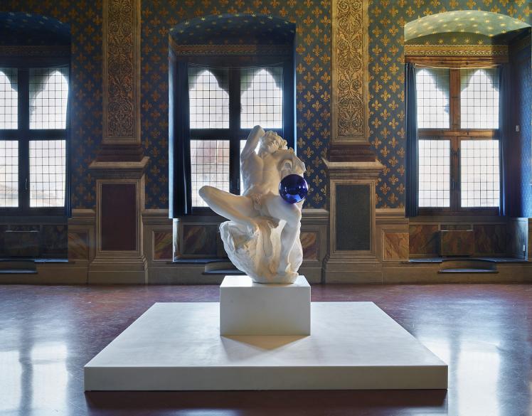 """A Palazzo Vecchio sarà esposta """"Gazing Ball"""" (Barberini Faun), opera realizzata nel 2013 appartenente alla serie di calchi in gesso di celebri sculture del periodo greco-romano cui Jeff Koons ha aggiunto, in posizione di precario equilibrio, una sfera di colore azzurro brillante e dalla superficie specchiante."""