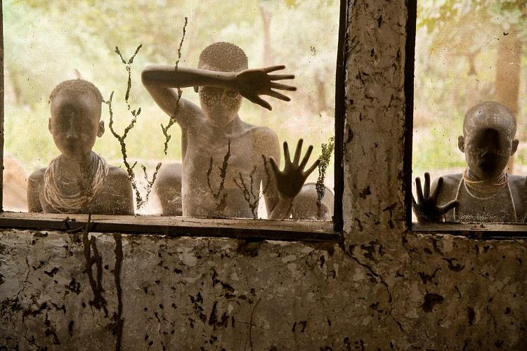 Bambini della tribù Kara che guardano attraverso le finestre, Omo Valley, Ethiopia, 2013 (Children from Kara tribe look through windows, Omo Valley, Ethiopia, 2013) ©Steve McCurry