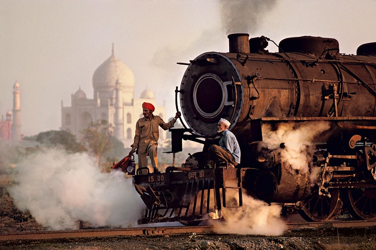 Operai su una locomotiva a vapore, India, 1983 (Workers on a steam locomotive, India, 1983) ©Steve McCurry