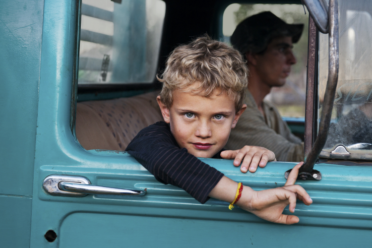A young boy looks out the window of a truck - Steve McCurry