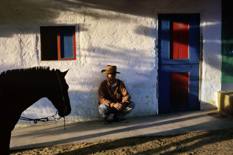 A man crouches against a wall - Steve McCurry