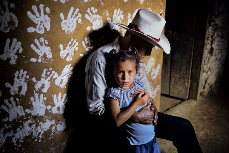 A man and child against a handprinted wall - Steve McCurry